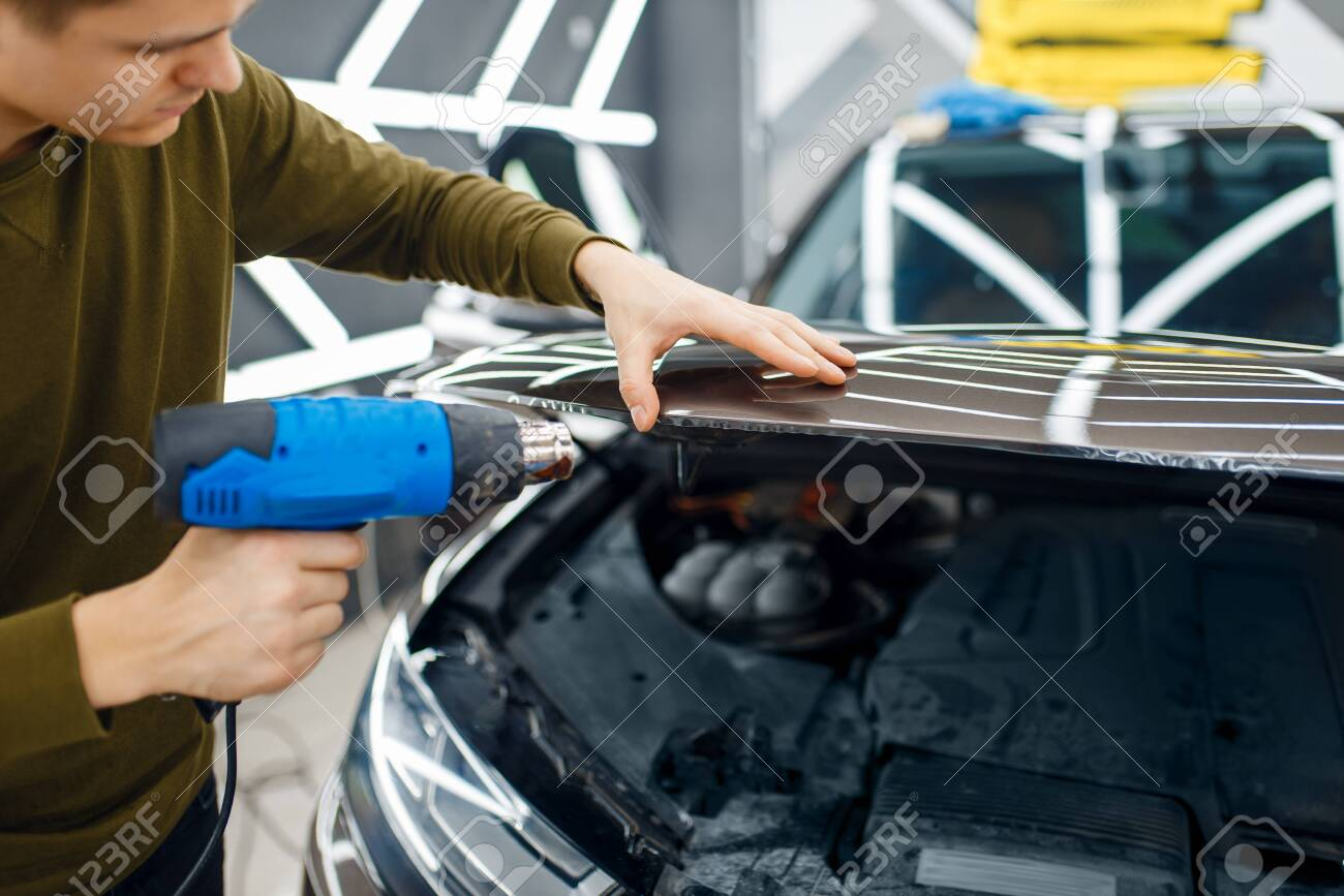 Male worker dries vinyl car protection film on hood. Installation of coating that protects the paint of automobile from scratches. New vehicle in garage, tuning procedure - 145090983