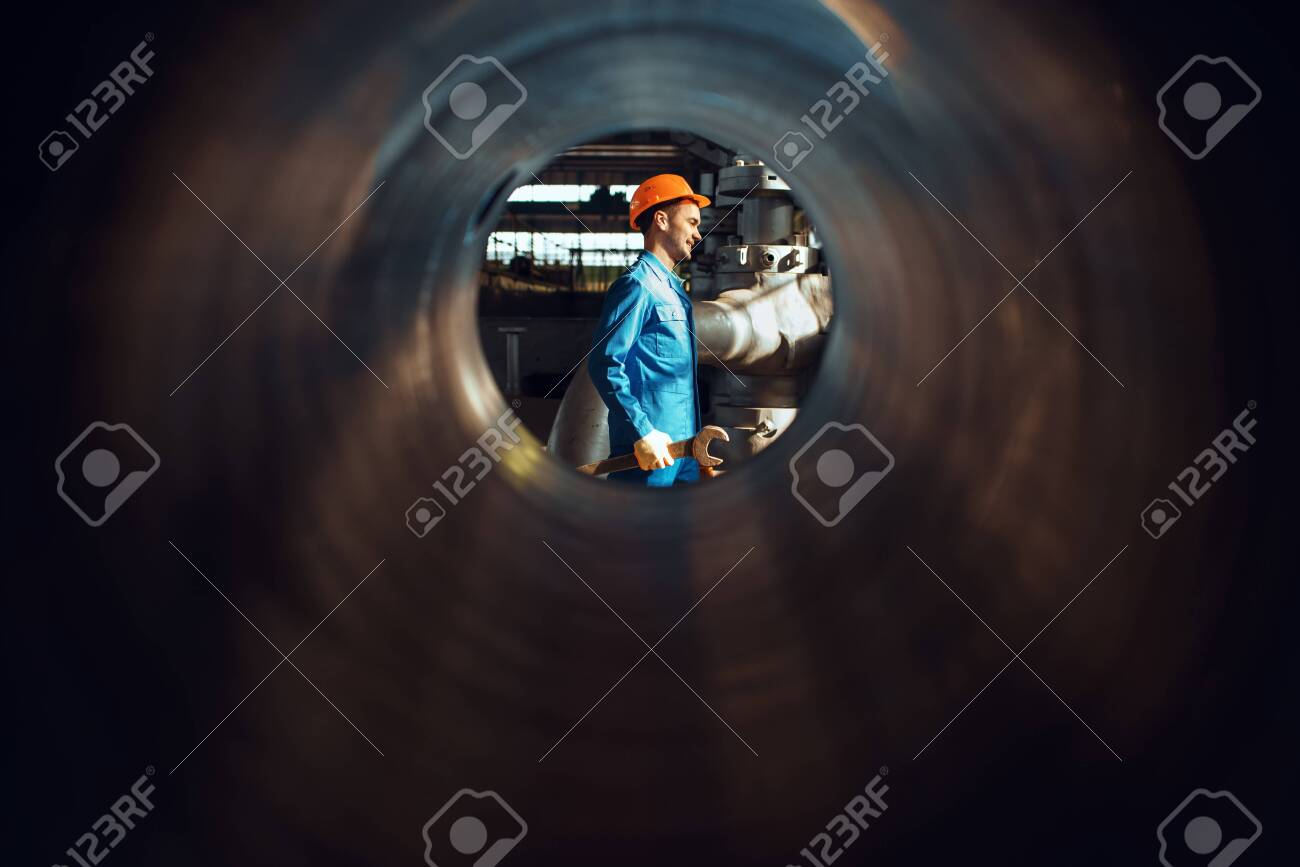 Worker with wrench on factory, view through tube - 148259406