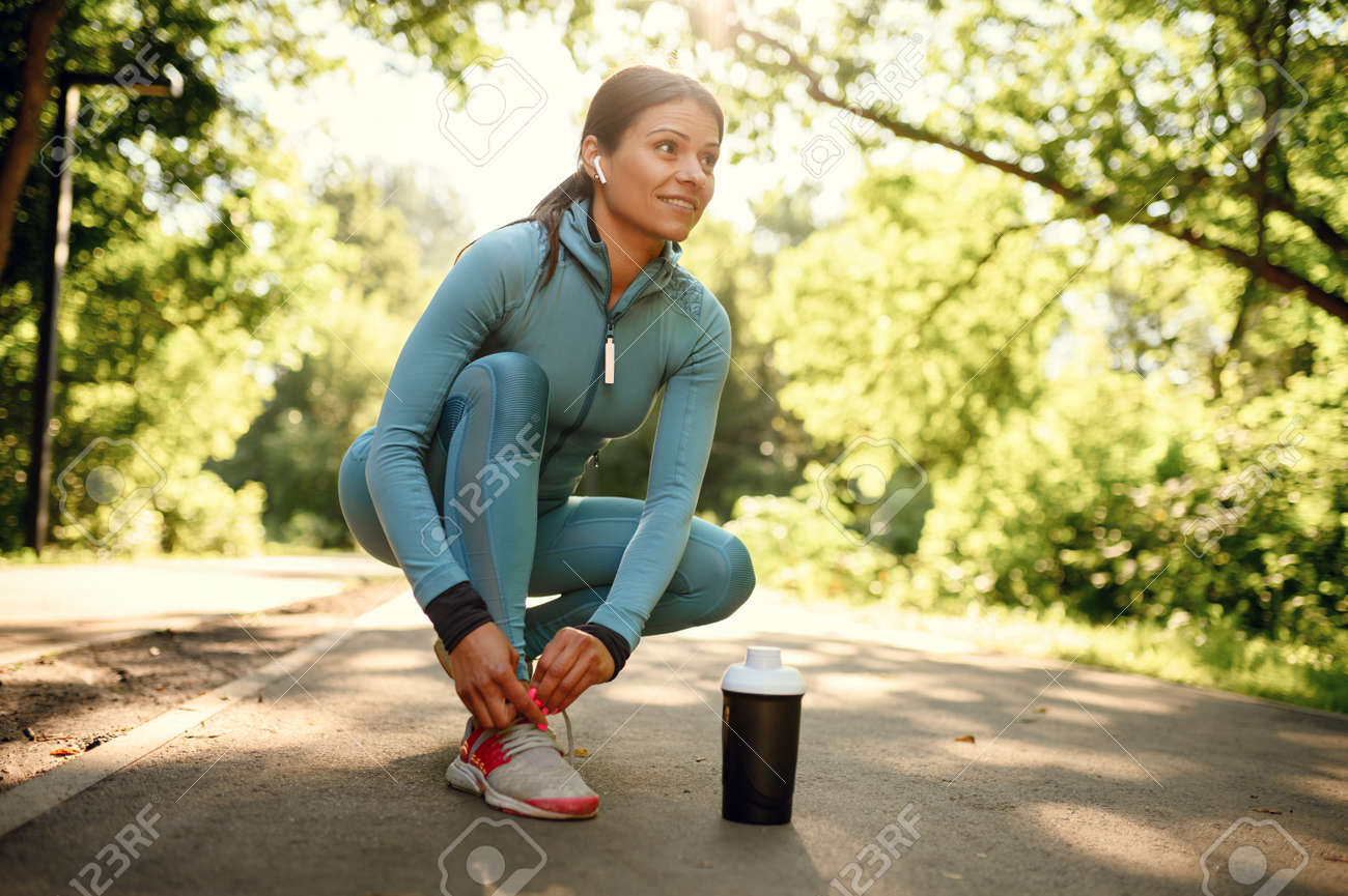 Workout in park, smiling woman in headphones - 159790245