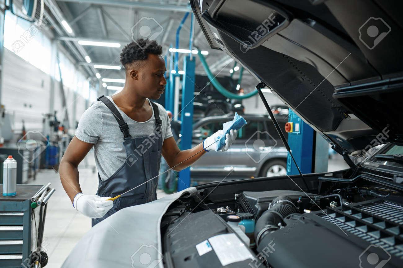 Male mechanic checks oil level, car service - 168382860