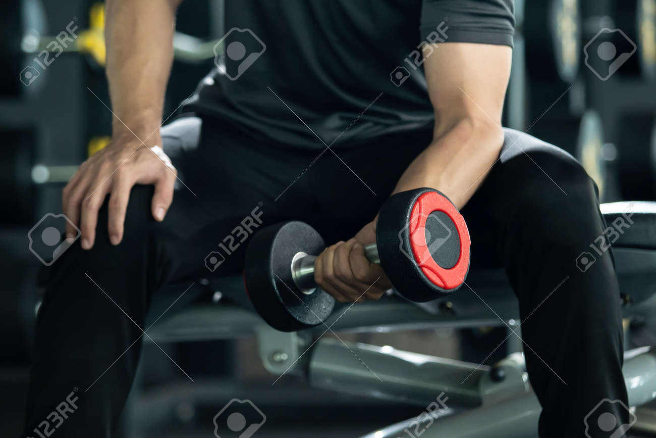 Asian young man practice weight training workout in the gym, body building exercise. Muscle building challenge concept. Strong sportsman lift up a dumbbell close up with copyspace. - 165970366