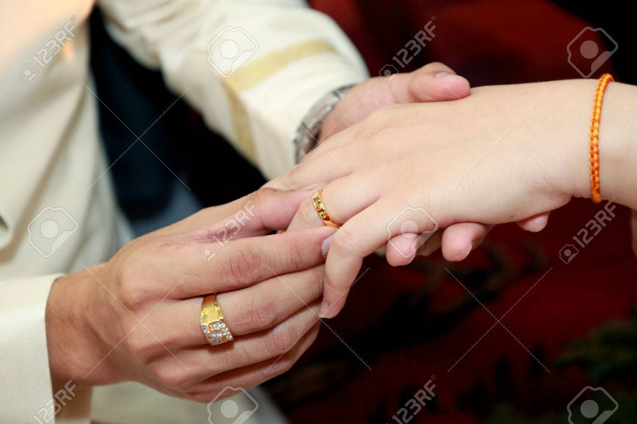 Thai Groom Wearing Wedding Ring For His Bride Hand Stock Photo