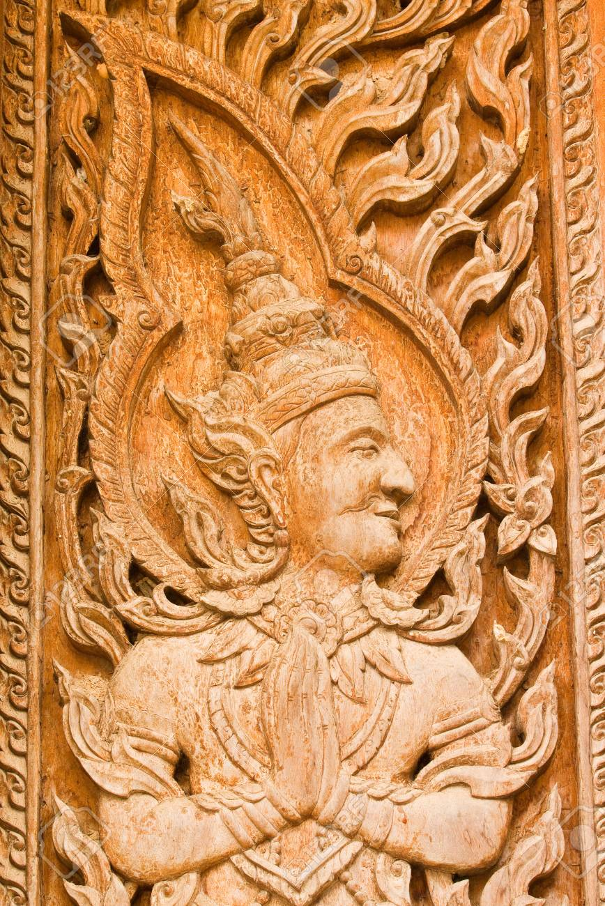 The old traditional thai art wood carvings on a door in a temple