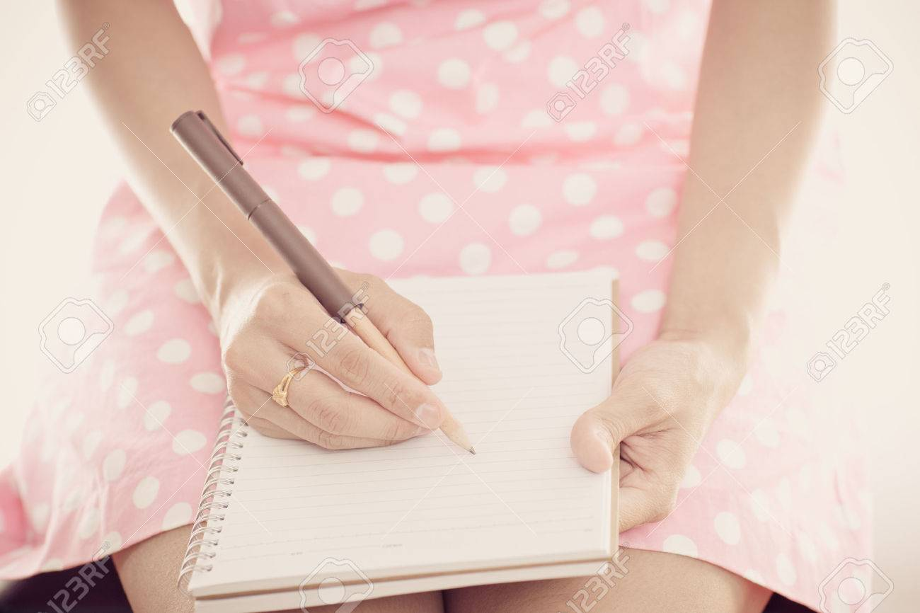 Young female is writing notes and planning her schedule Stock Photo - 30962627