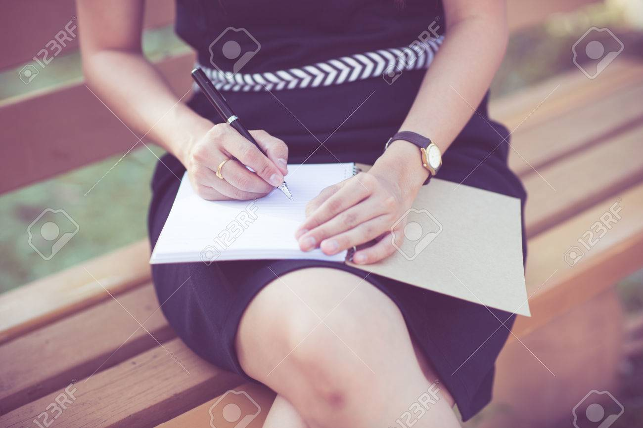 Young business woman planing, writing and reviewing report at city park. Stock Photo - 31857306