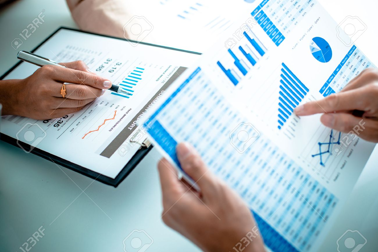 Business people discussing the charts and graphs showing the results of their successful teamwork Stock Photo - 36704612