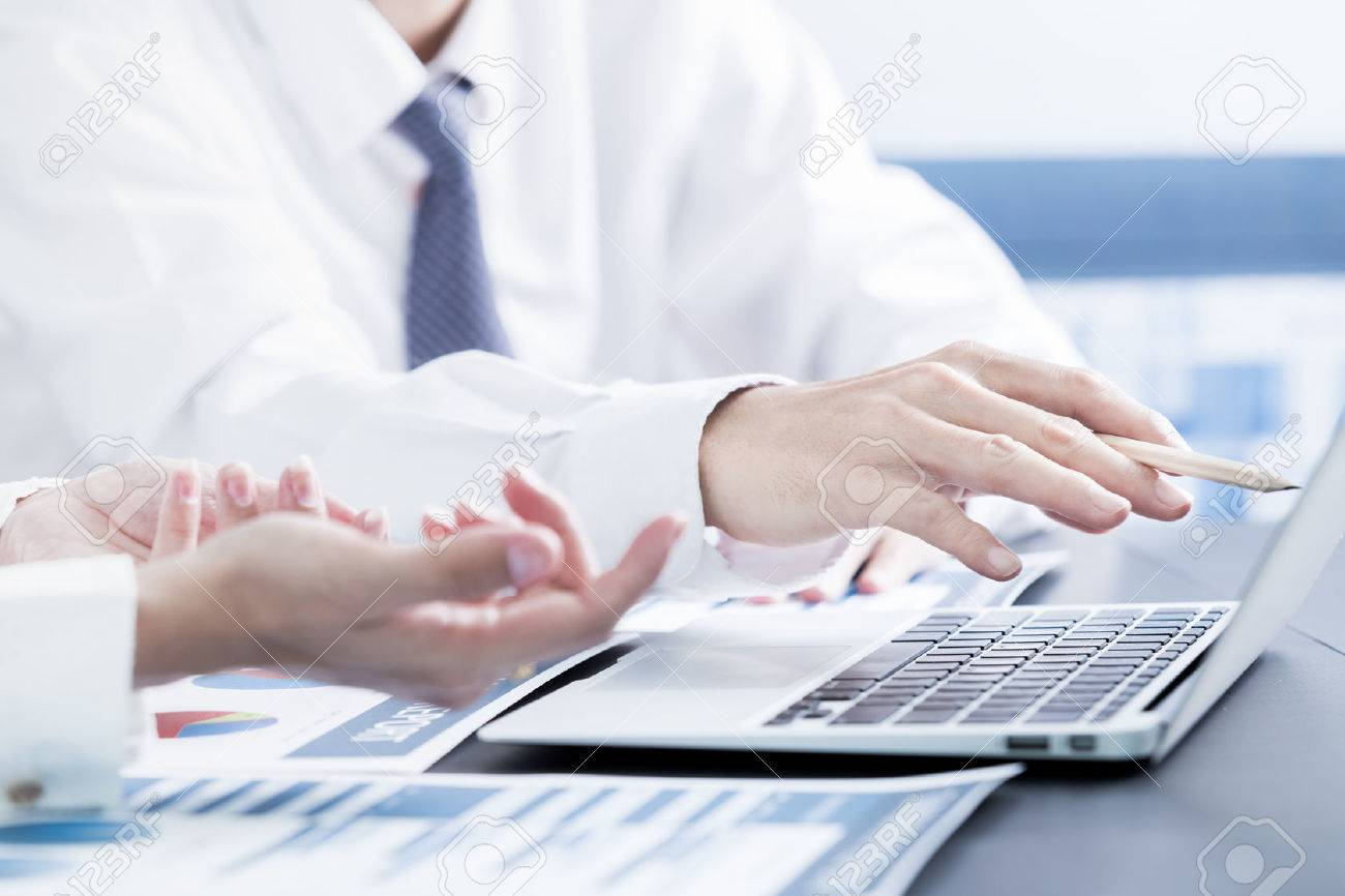Business people discussing the charts and graphs showing the results of their successful teamwork Stock Photo - 51957255