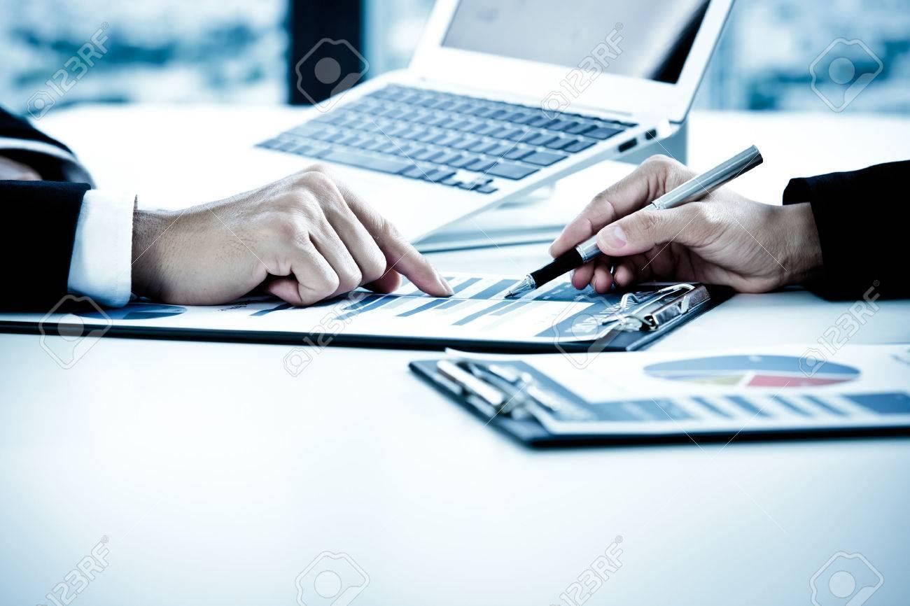 Les gens d'affaires discutant des tableaux et des graphiques montrant les résultats de leur travail d'équipe réussie Banque d'images - 54430333