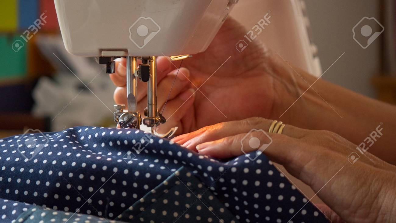 female hand using sewing machine stitching fabic - 80864875