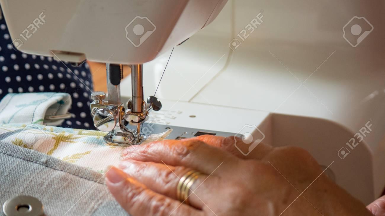 female hand using sewing machine stitching fabic - 80864854