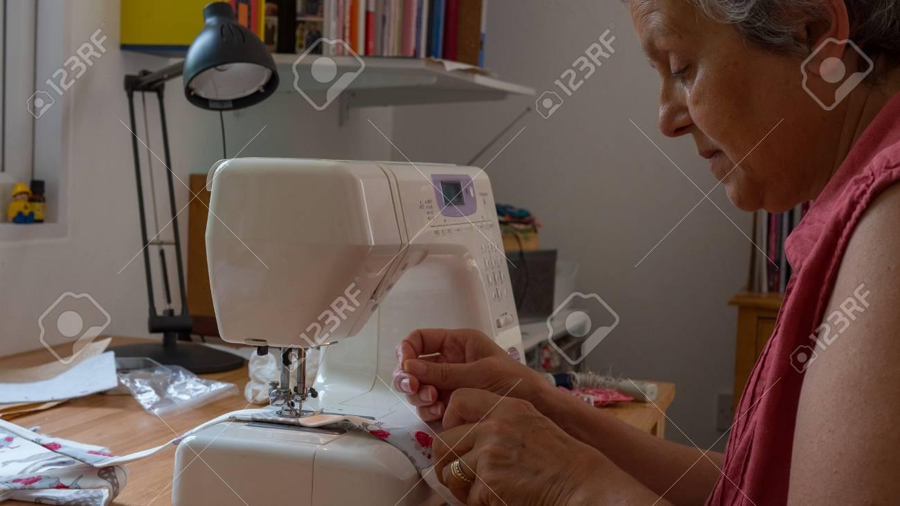 elderly woman using sewing machine stitching fabic - 80812805