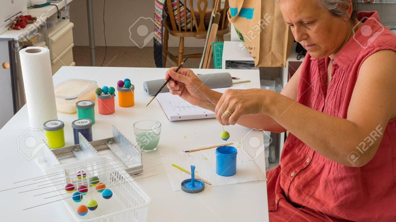 woman painting polymer clay beads. Handmade workshop composition of clay, beads, tools and paint - 80864877