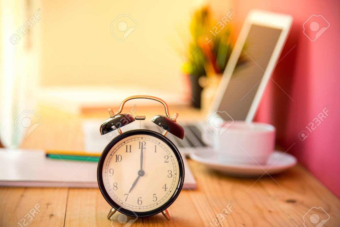 Alarm at 7 o'clock with blur laptop and cup of tea on table background. Good morning and start of new work day. Business concept. Banque d'images - 84337677