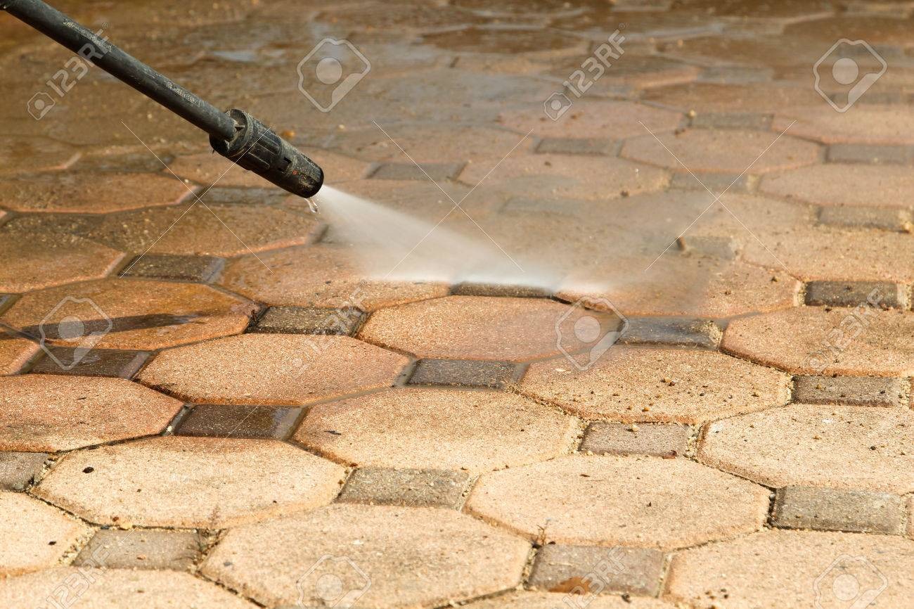 Cleaning concrete block floor by high pressure water jet. - 65322609