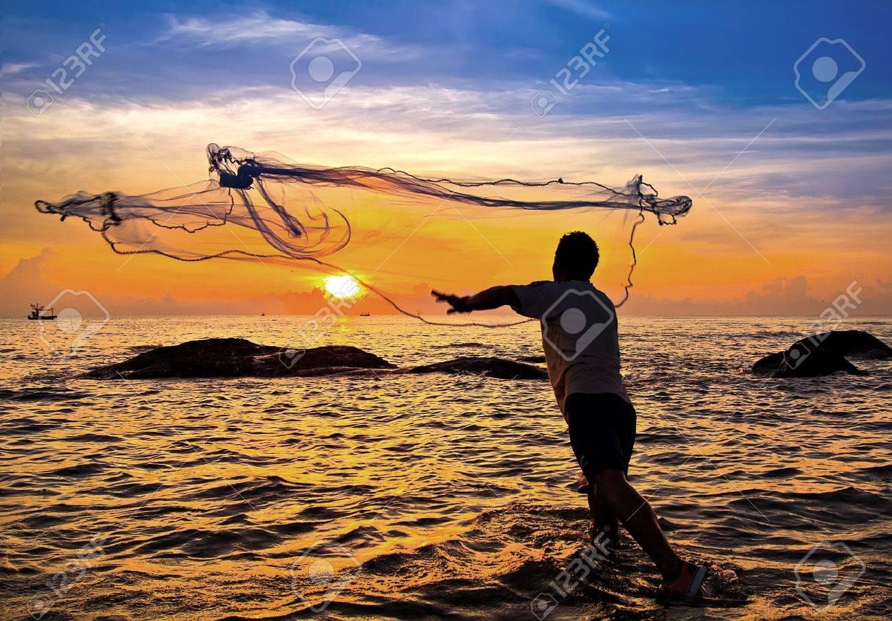 throwing fishing net during sunset , thai - 12663165