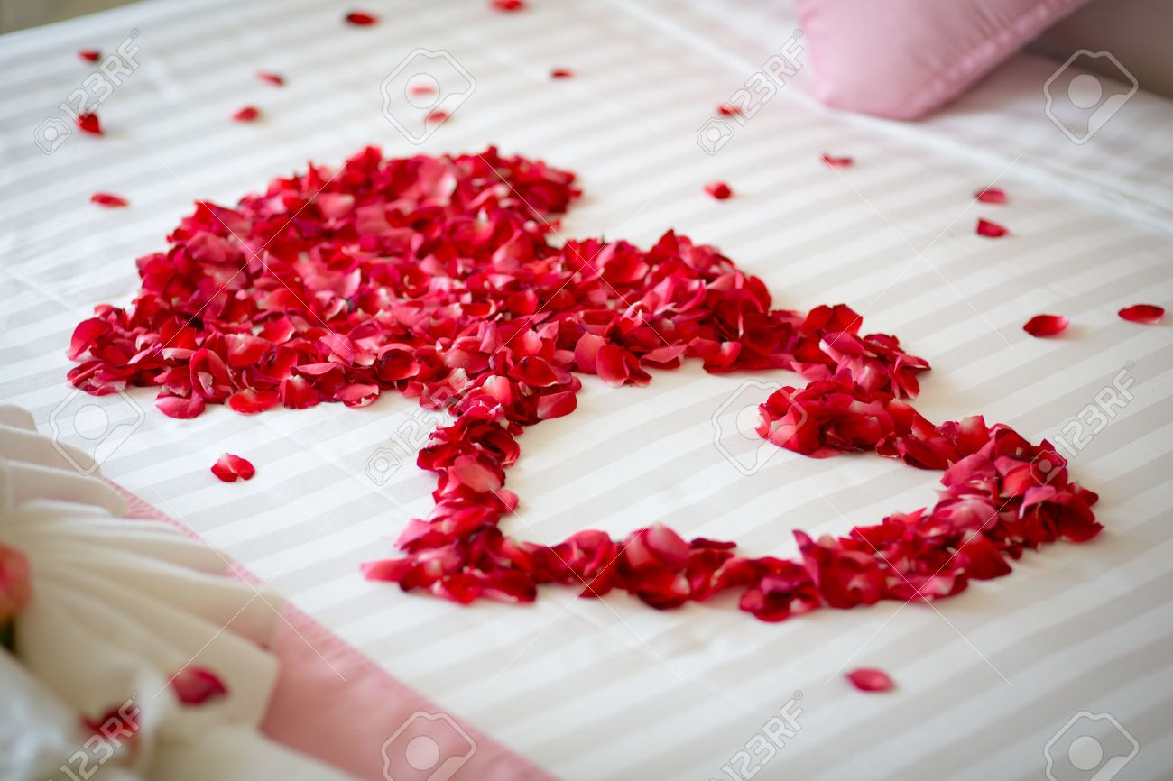Honeymoon Wedding Bed Topped With Rose Petals Stock Photo