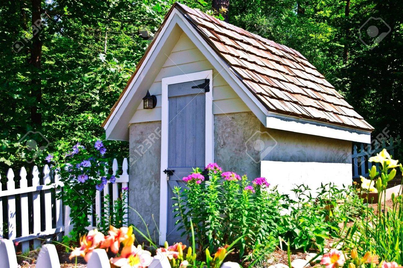 a small garden shed with flowers blooming around it and a white