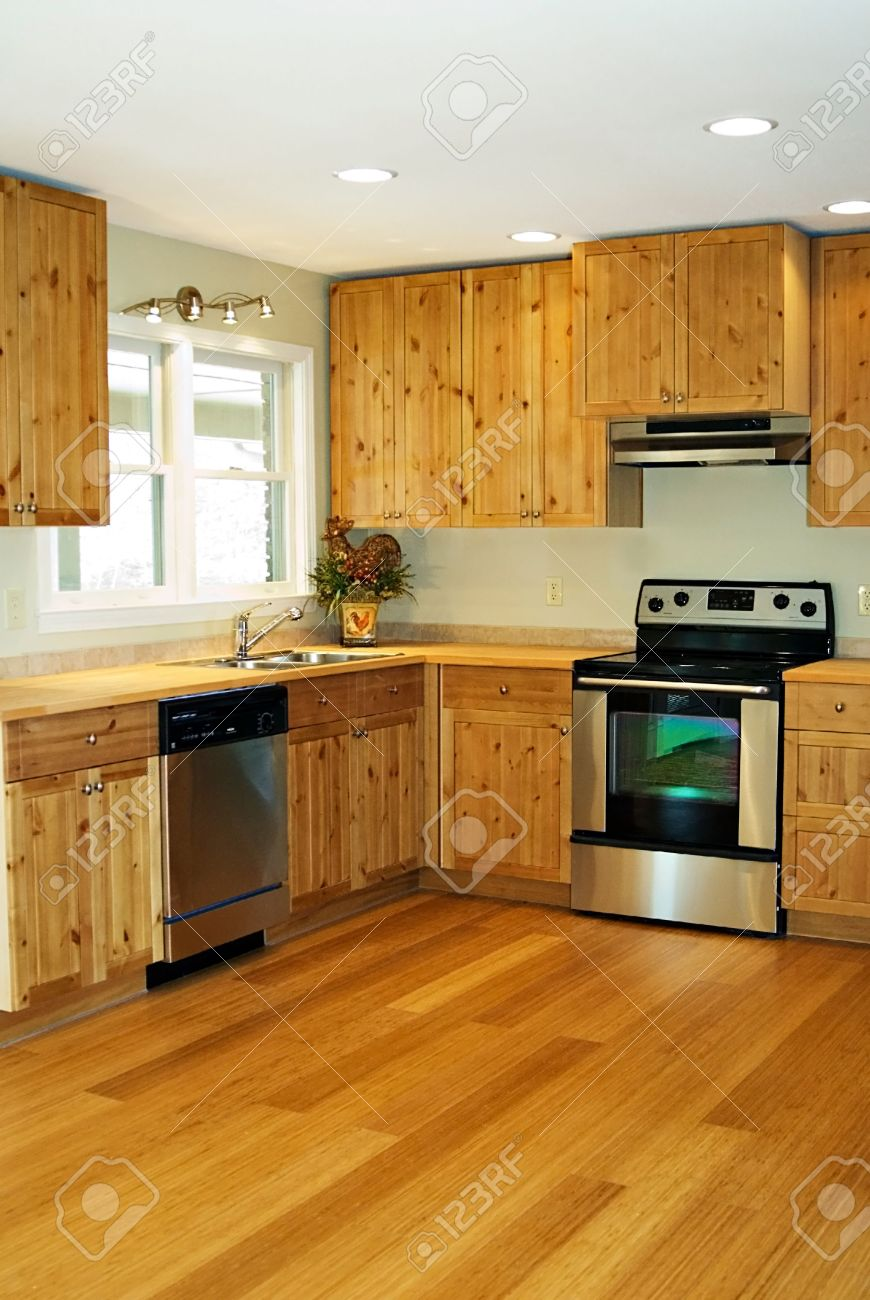 A Small, New, Kitchen With Bamboo Flooring And Pine Cabinets. Stock Photo