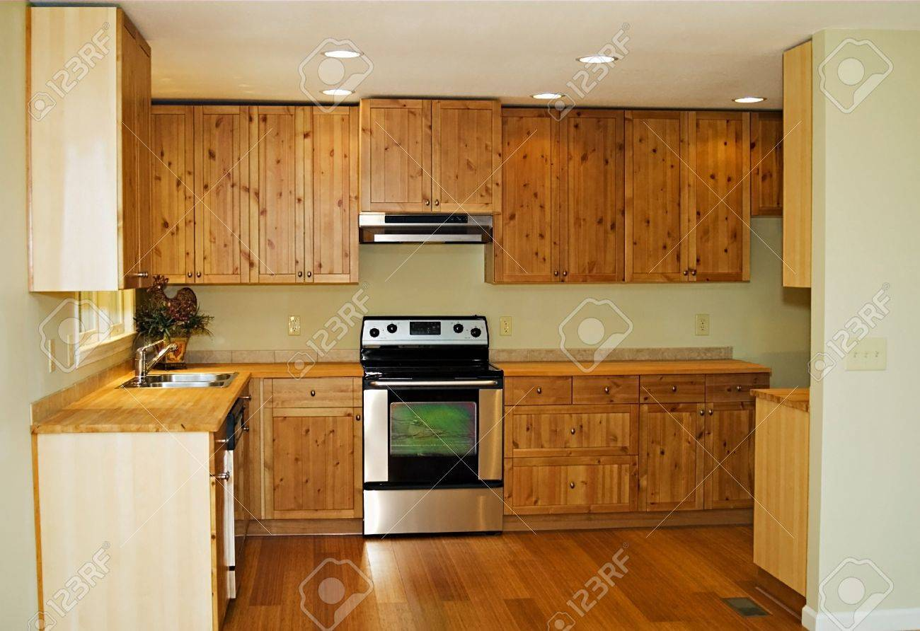 The interior of a new, small, kitchen with bamboo flooring and pine cabinetry. Stock Photo - 7899703
