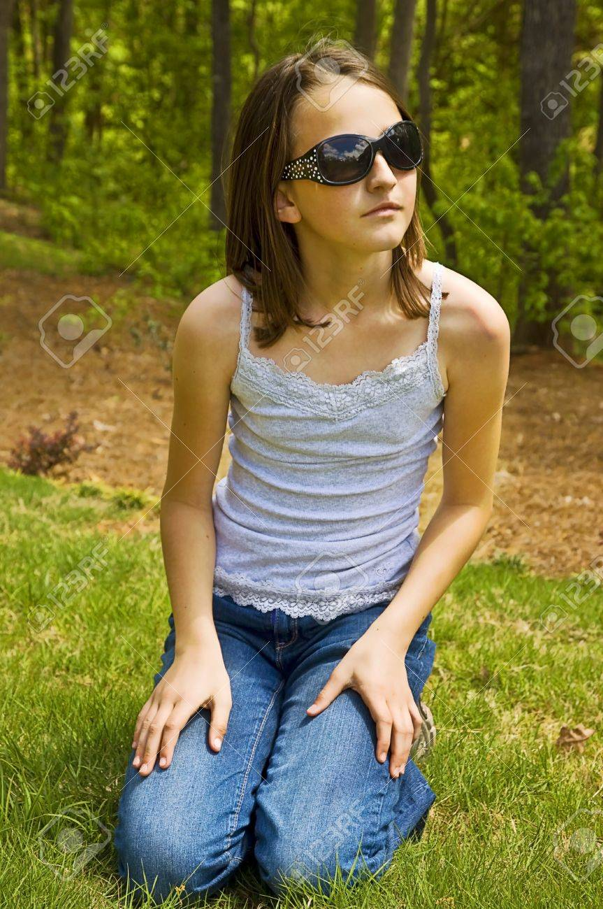 A cute young girl outside with stylish sunglasses, she has a thoughtful expression. Stock Photo - 9379378