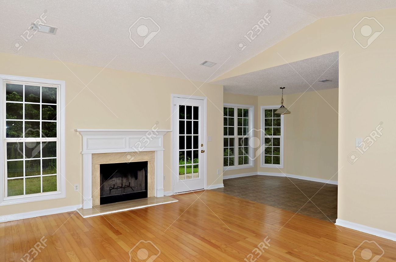 Stock Photo   Wood Burning Fireplace In A Greatroom With Oak Floors Flanked  By A Window And A French Door.