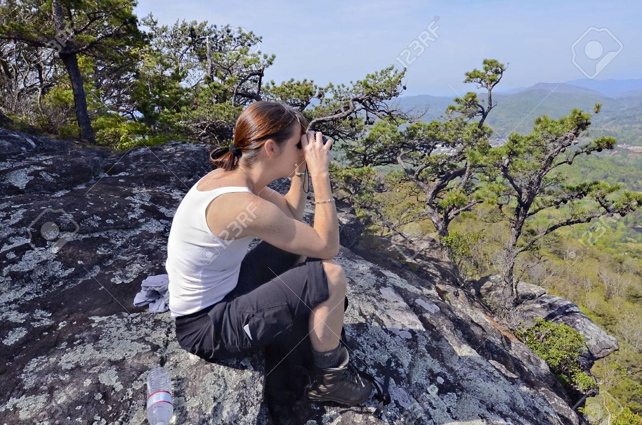 Eine frau wanderer auf einem felsen übersehen mit ihrem fernglas