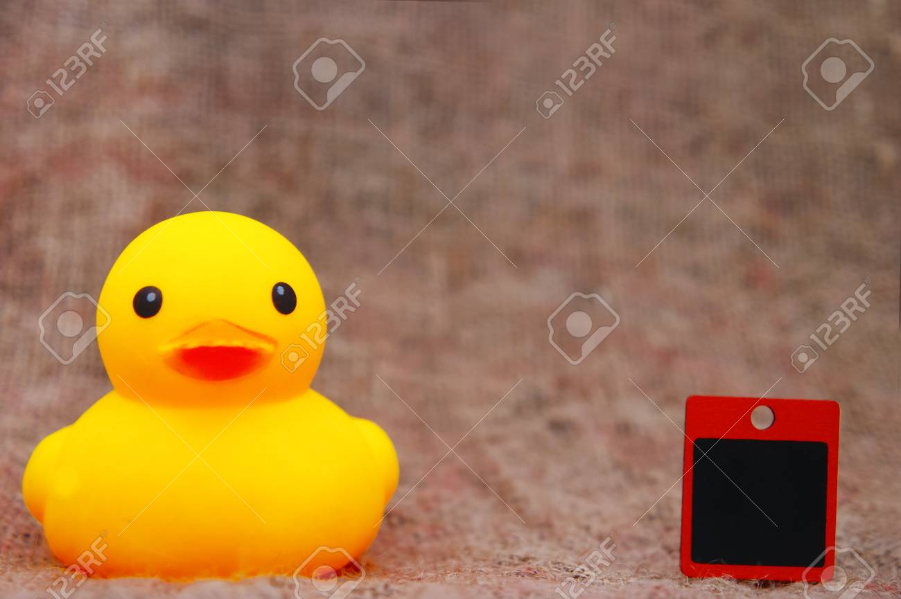 Yellow Duck Toys And Blank Cardboard Over Sackcloth Stock Photo ...