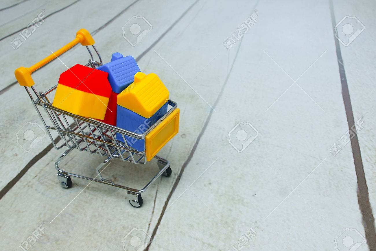 Toy House In Shopping Cart Over Wooden Floor