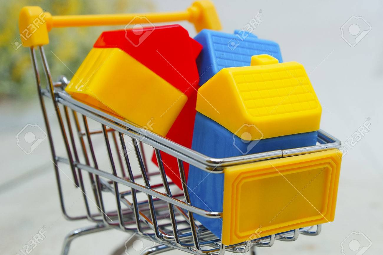 Close Up View Of Toy House In Shopping Cart Over Wooden Floor