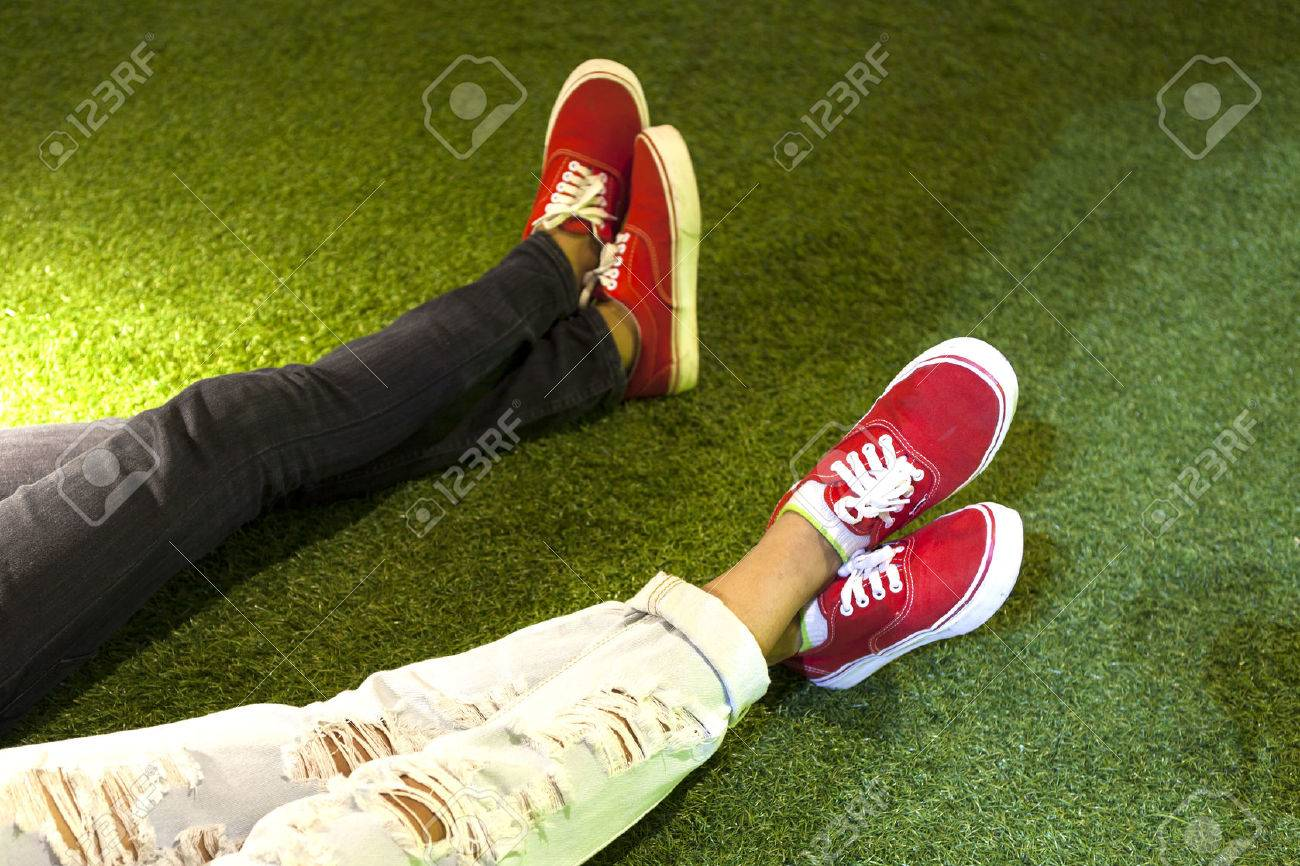 a08ae17b5 Stock Photo - two couple legs wearing red shoes, sweetheart, love you on  grass