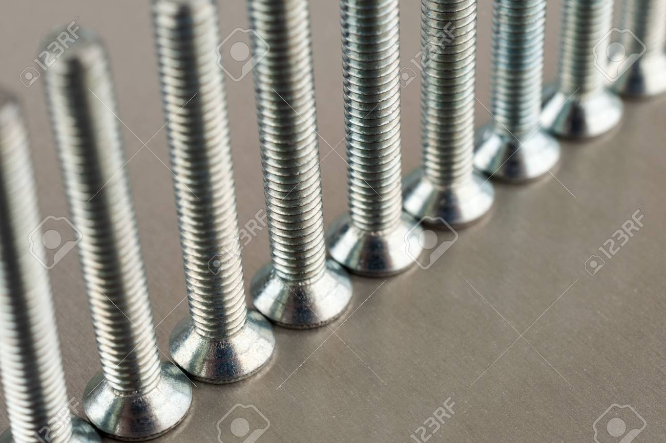 An even number of metal screws standing on a metal sheet Stock Photo - 17251756