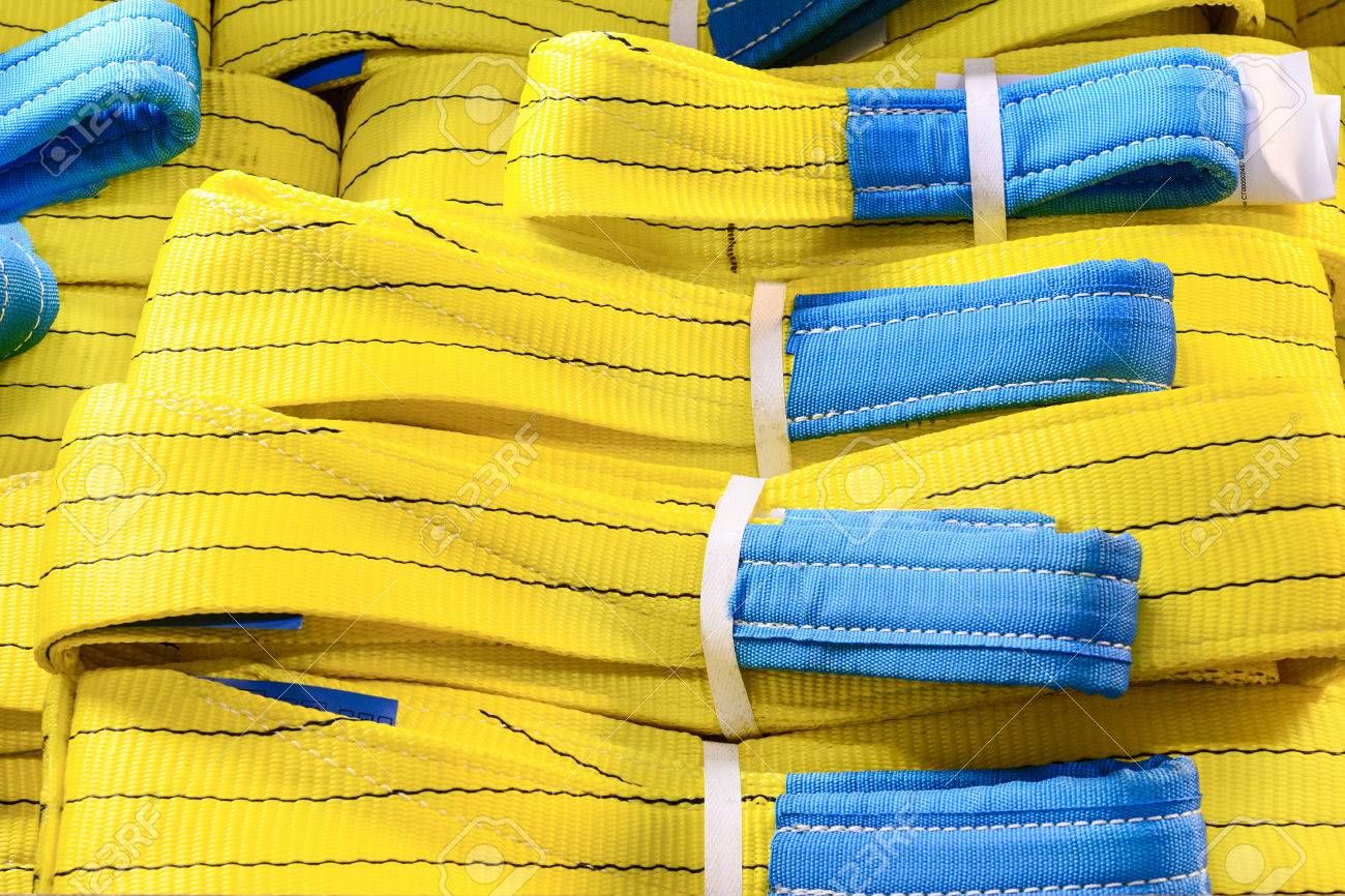 Yellow nylon soft lifting slings stacked in piles  Warehouse