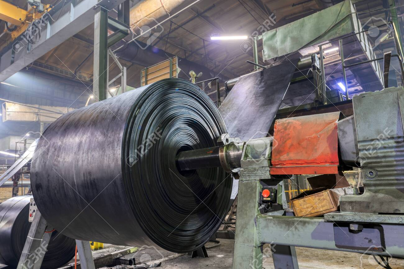 Interior of a factory for manufacturing rubber conveyor belts. Large rolls of black rubber tape. - 141631277