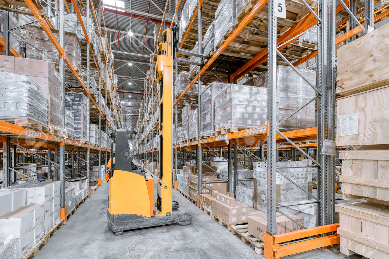 Large warehouse. Tall and long metal racks filled with various boxes, containers and drawers - 156084178