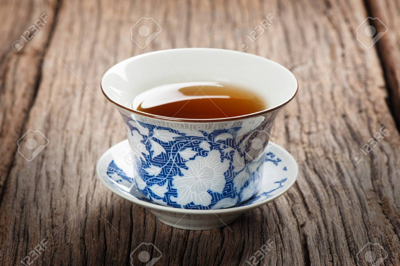 tea cup with tea leaf isolated on wooden plank - 37681115