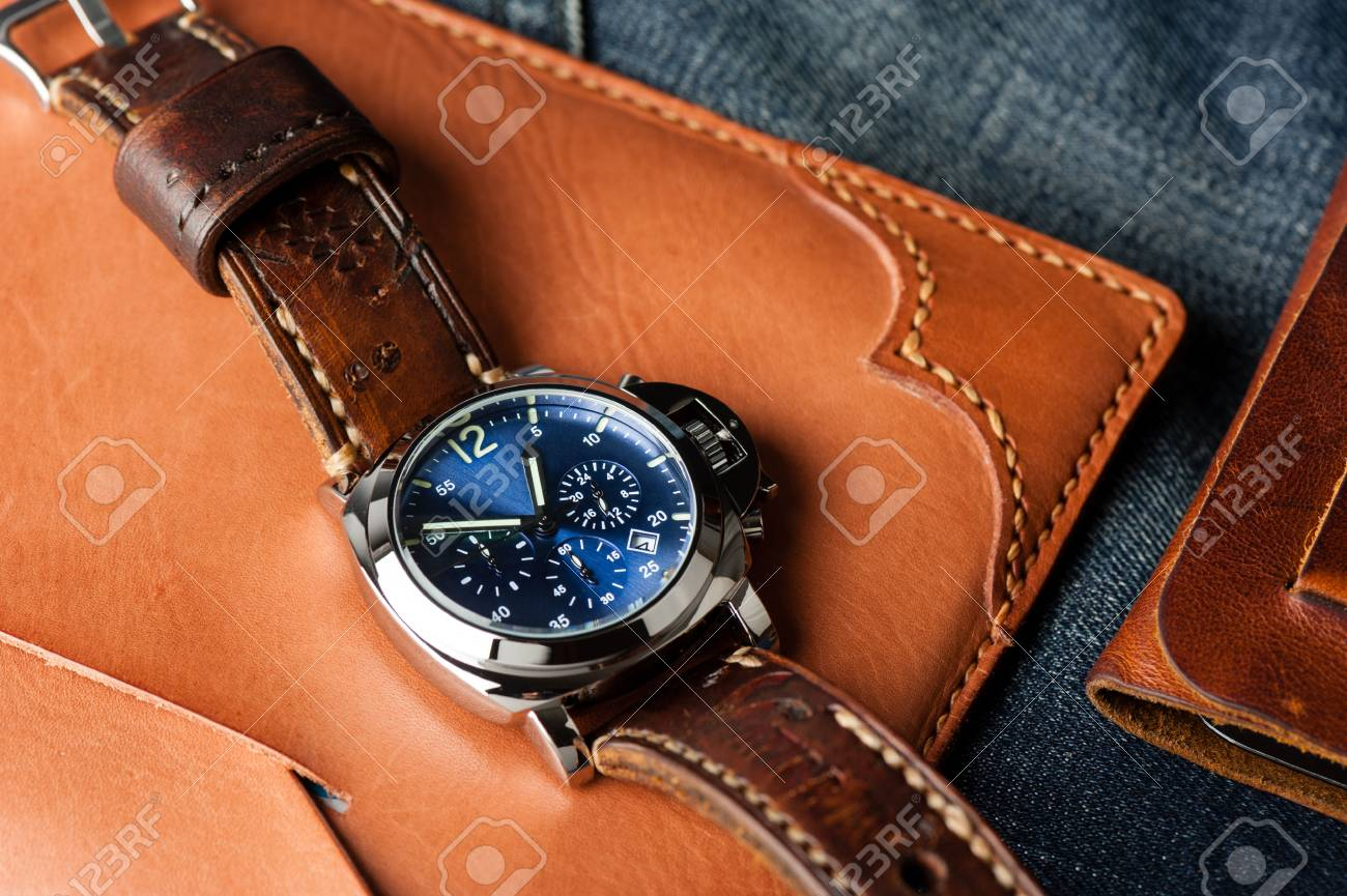 luxury fashion watch with blue dial and brown leather watch band..