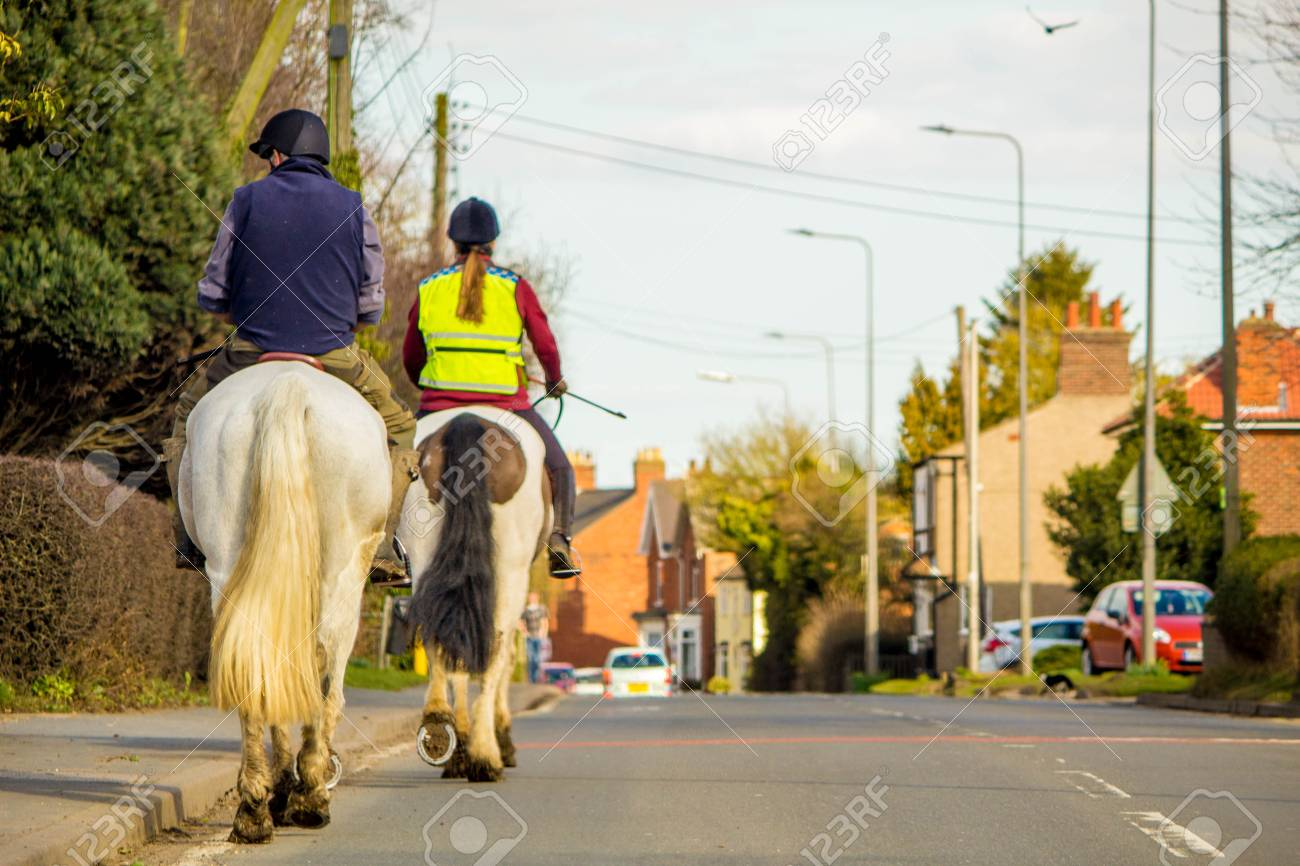 Two horse riders travel through a small village, on the main road. - 99084210
