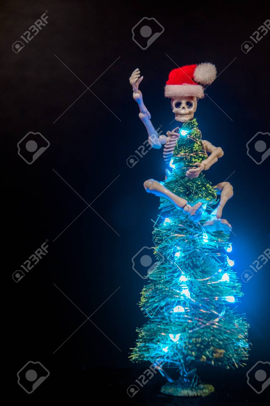 Christmas Skeleton.A Skeleton Hanging Onto The Top Of A Lit Up Christmas Tree