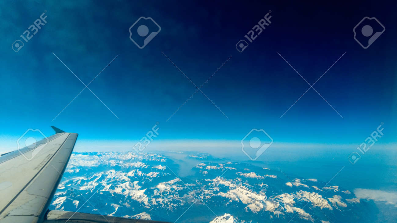 A view from a passenger window of a large aircraft traveling across the world on a holiday or business trip. - 166119434