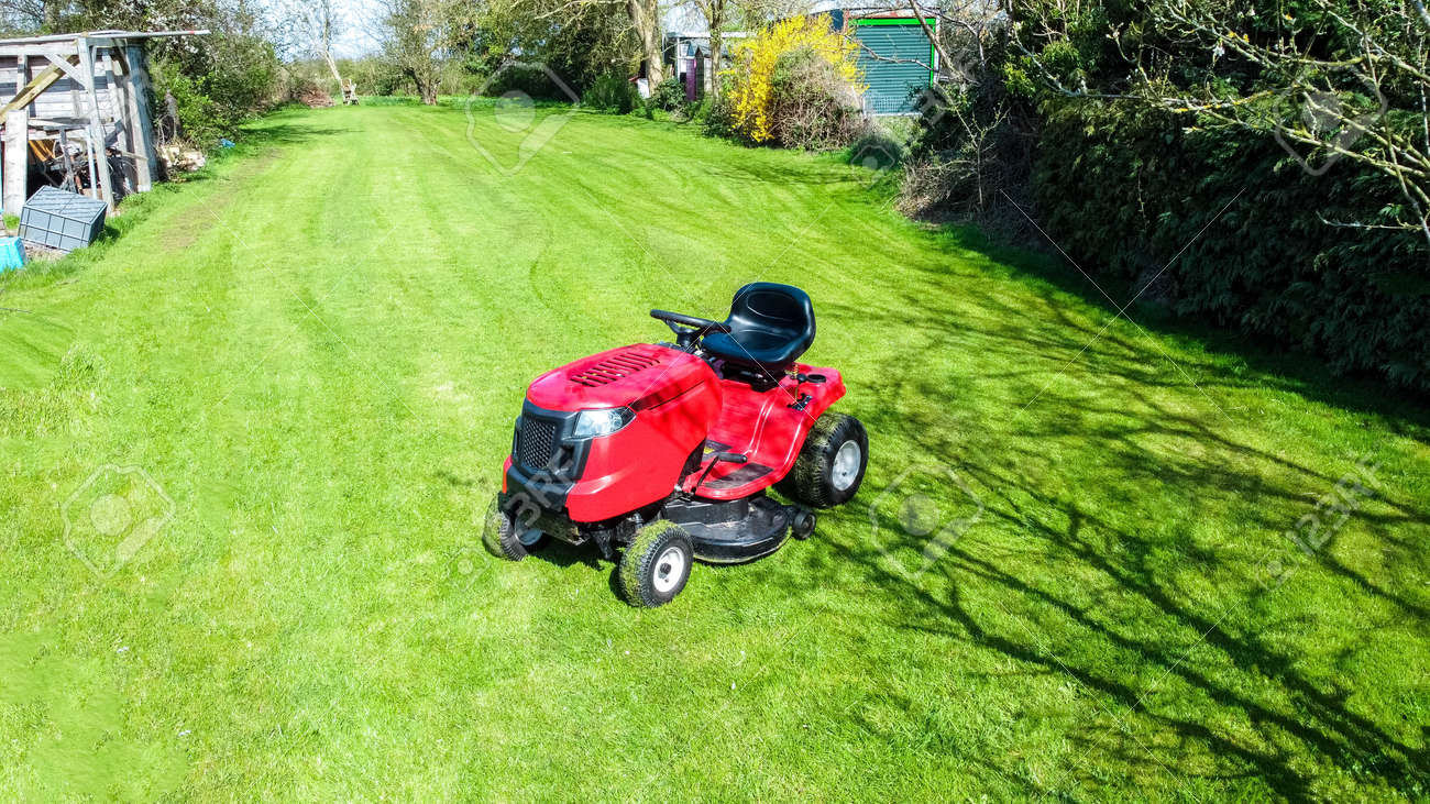 A view of a large ride along lawn mower cutting the grass of a large garden, at the back of a small property. The sun shining above during spring time. - 168149661