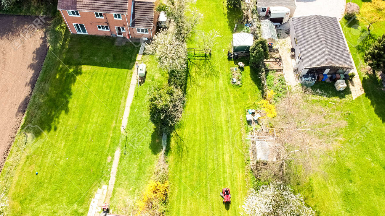 A long garden at the rear of a small property, in England, United Kingdom. The view seen from a drone high up above the property. - 168149671