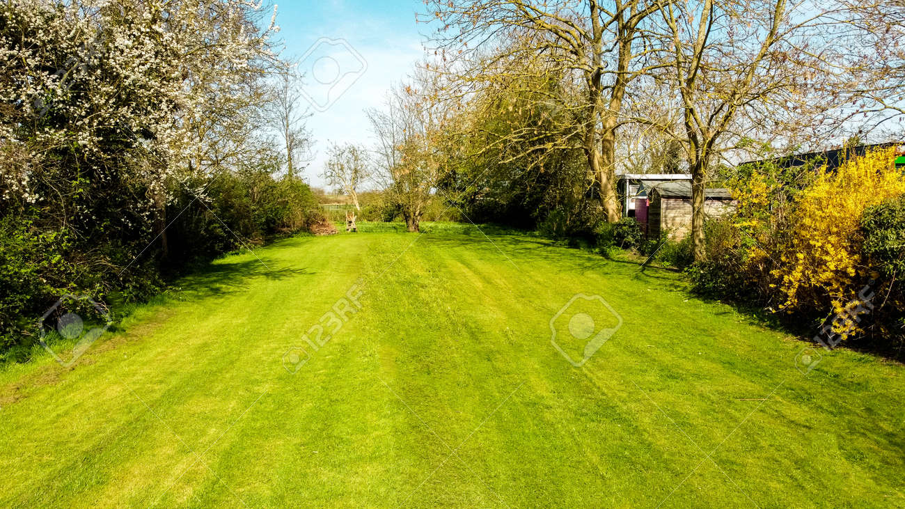 A long garden at the rear of a small property, in England, United Kingdom. The view seen from a drone high up above the property. - 168149674