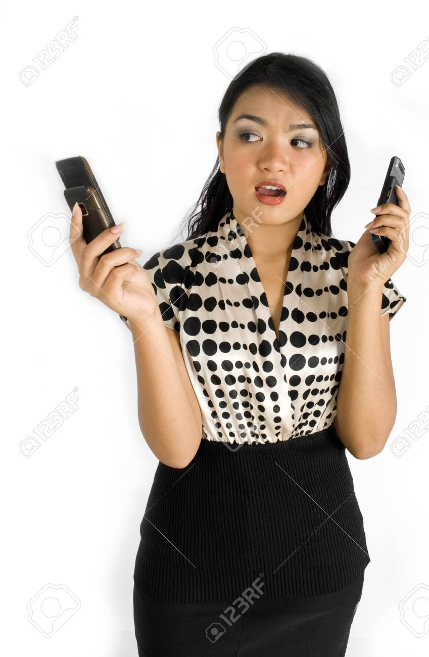 Female asian business woman shocked and busy with a pair of mobile phones Stock Photo - 4756362
