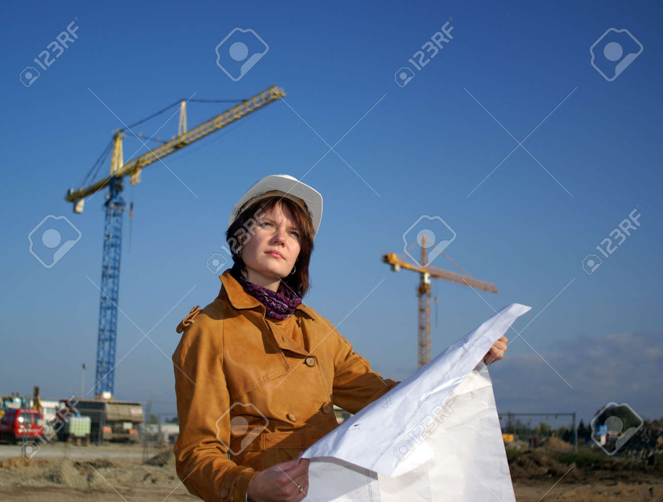 Young architect looking at blueprint in front of construction site against blue sky Stock Photo - 3632864