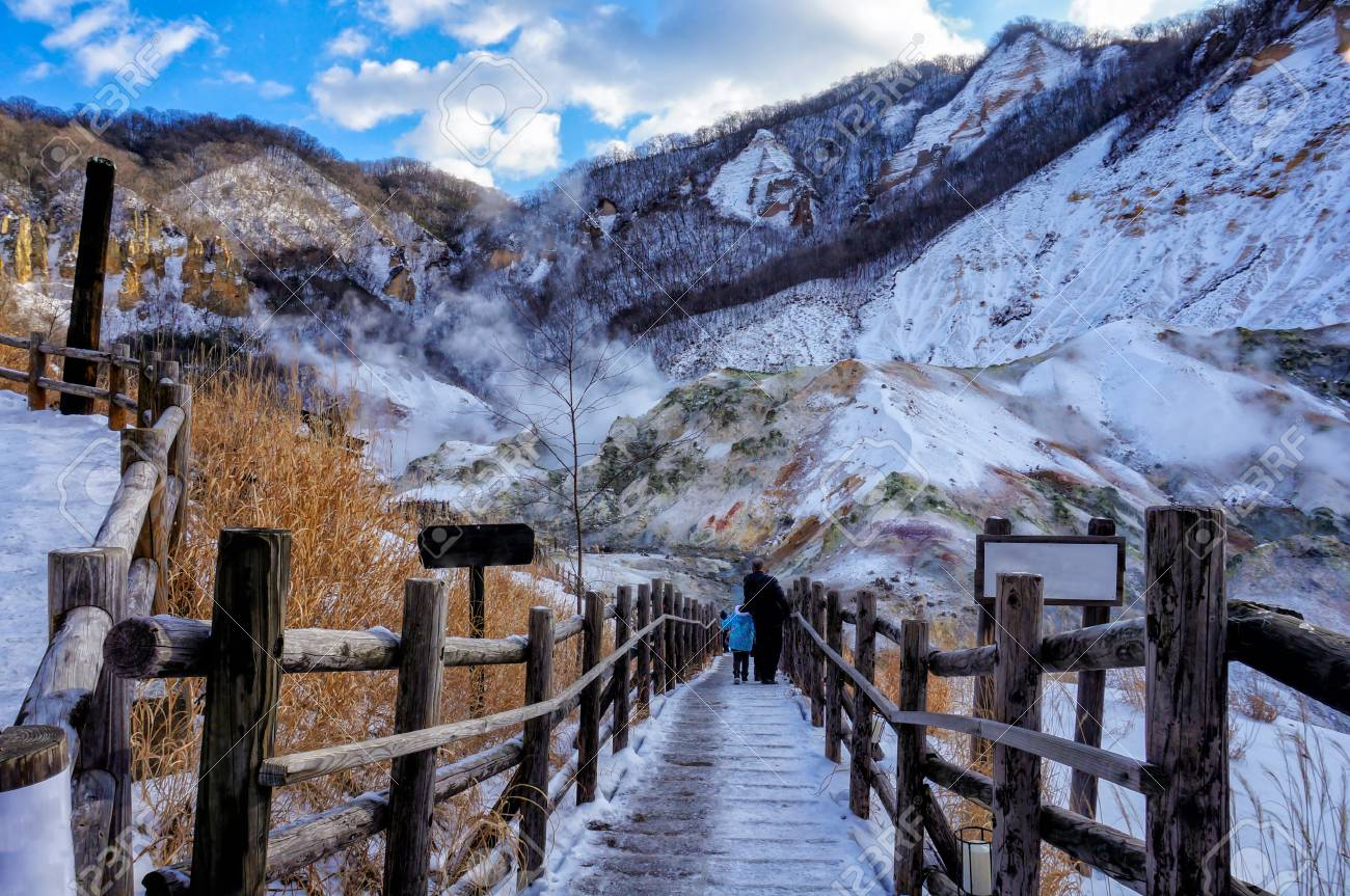 """Traveler walking into Jigokudani, known in English as """"Hell Valley"""" is the source of hot springs for many local Onsen Spas in Noboribetsu, Hokkaido, Japan in winter - 92441676"""