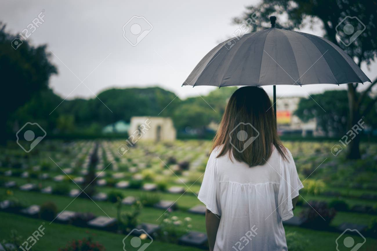 Young woman holding black umbrella mourning at cemetery - 110824837