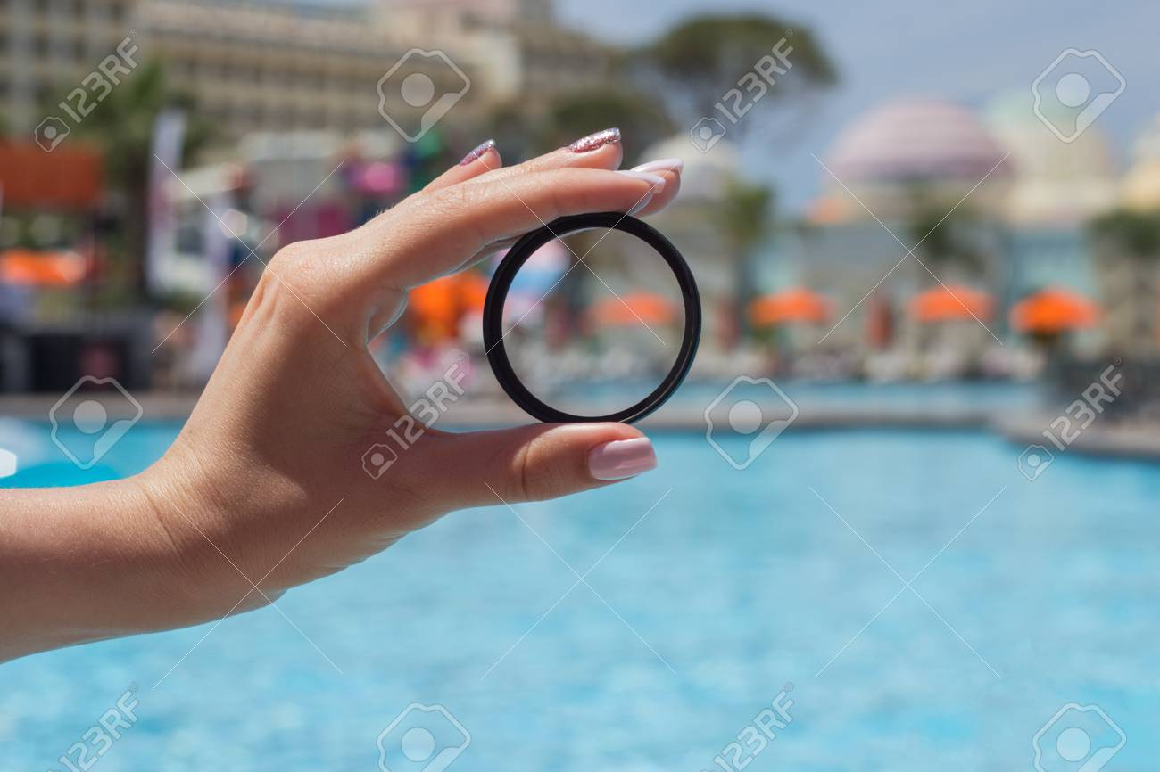 photo filter in the hand of a girl near the pool close-up - 102141271