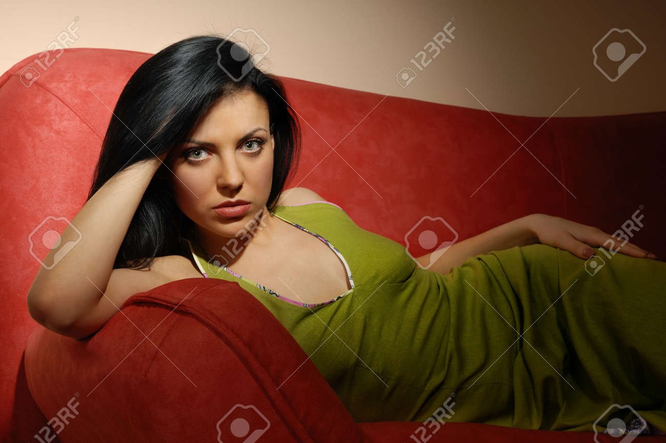 Elegant model laying on the red sofa in dark room Stock Photo - 2791282