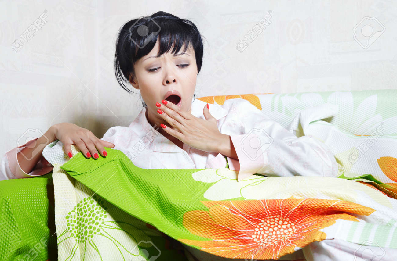Yawning lady on the bed covered by colorful blanket Stock Photo - 5627195