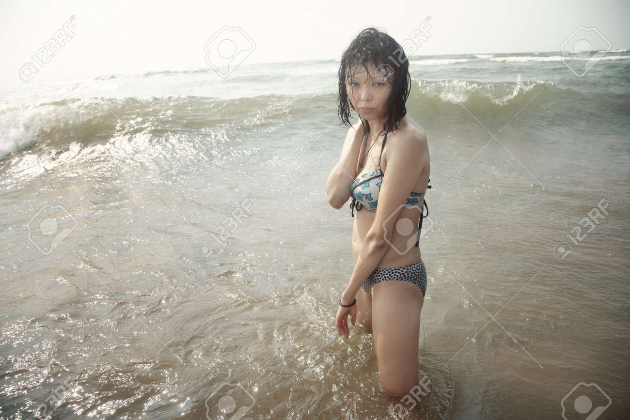 wet brunette lady in bikini standing in the water stock photo